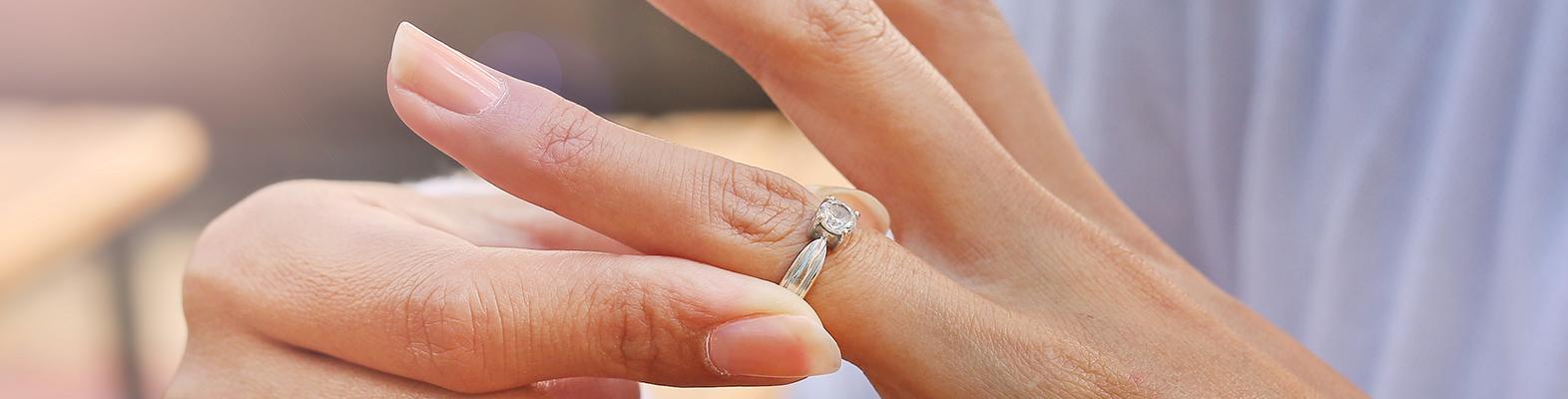 woman taking off wedding ring indicating divorce