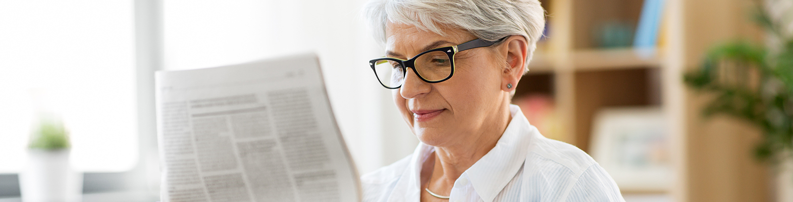 older woman reading the newspaper