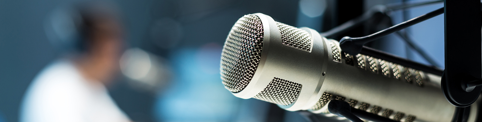 microphone with guy in radio station blurred in background