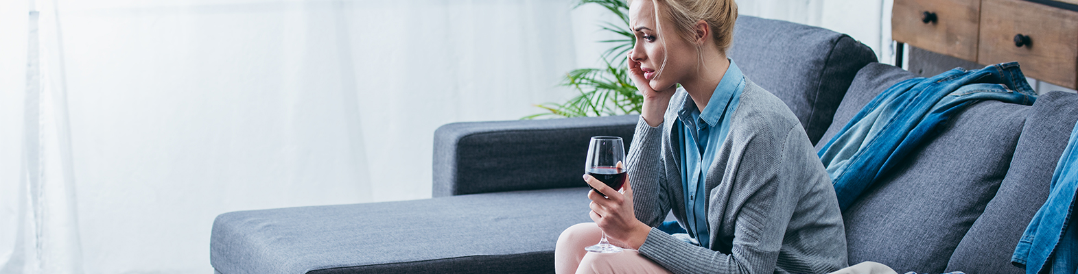 female worried, drinking a glass of wine