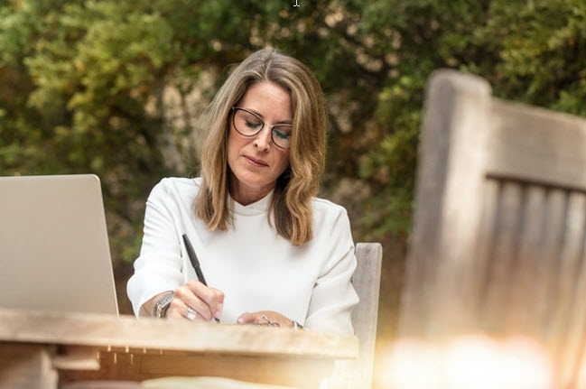 middle aged woman outdoor sitting at table writing
