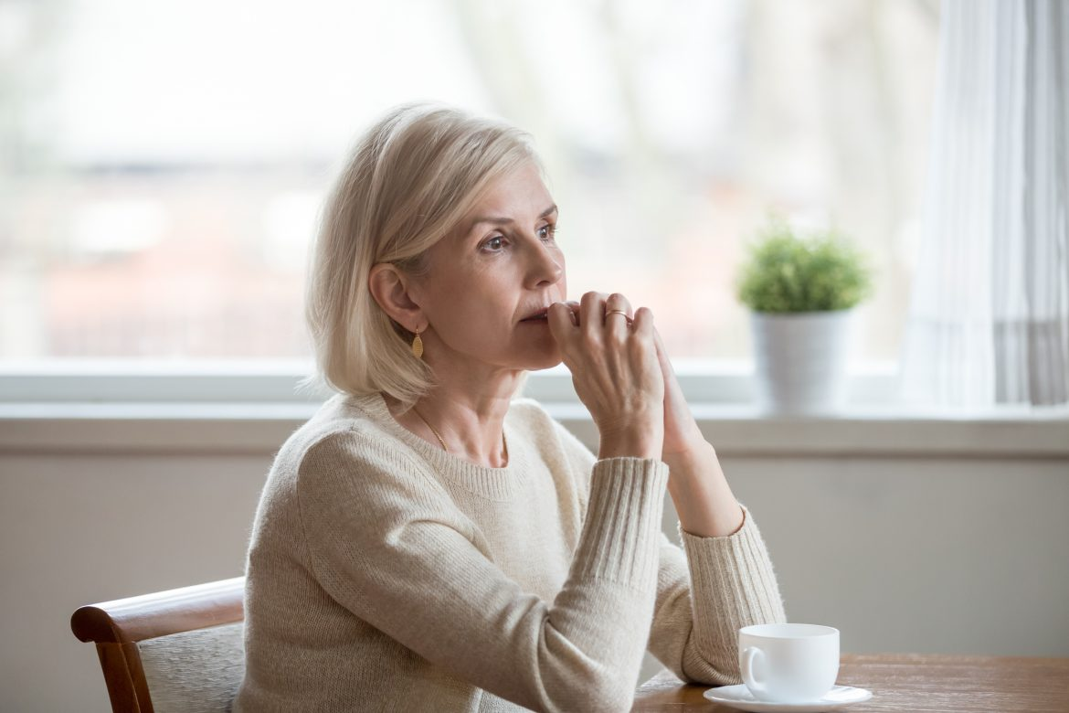 middle aged woman sitting at table drinking tea and thinking
