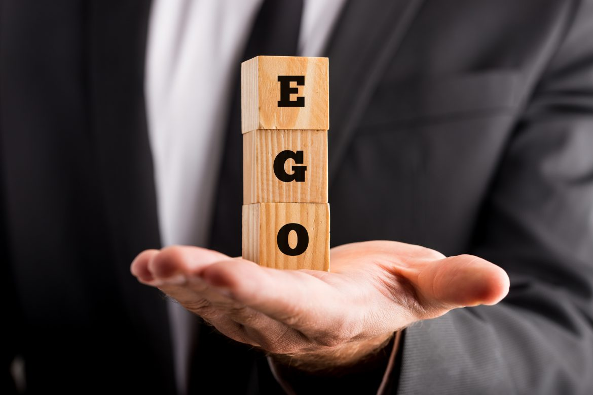 man holding wooden blocks marked with 'EGO'