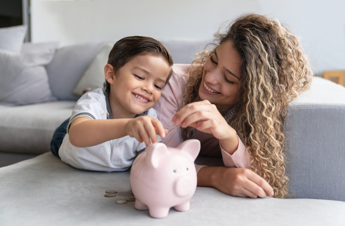 mother and son putting coins into piggy bank