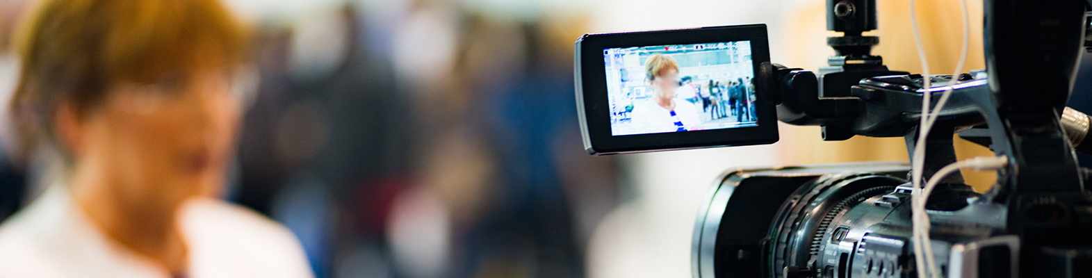 video camera with woman blurred in background