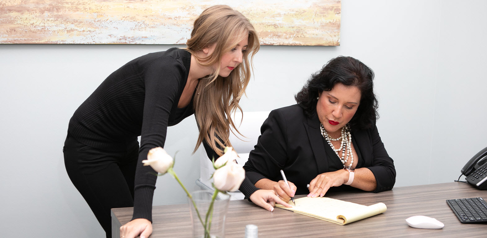 Melissa Valentine and Susan Birch looking at legal documents
